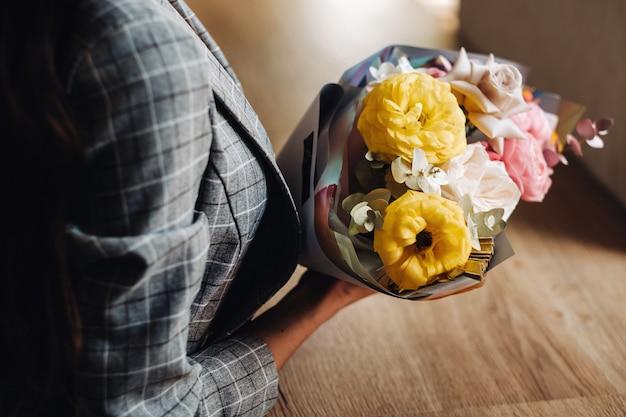 Close-up van de handen van een meisje in een café met een boeket ernaast. beckett ligt op het aanrecht in het café en naast de handen van het meisje.
