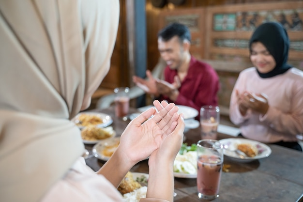 Close-up van de handen van een moslimvrouw die een hoofddoek draagt tijdens het bidden