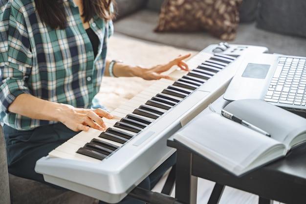 Close-up van de handen van een onherkenbare jonge vrouw die op afstand elektrische piano speelt met een laptop terwijl ze thuis werkt. online onderwijs en vrije tijd concept.