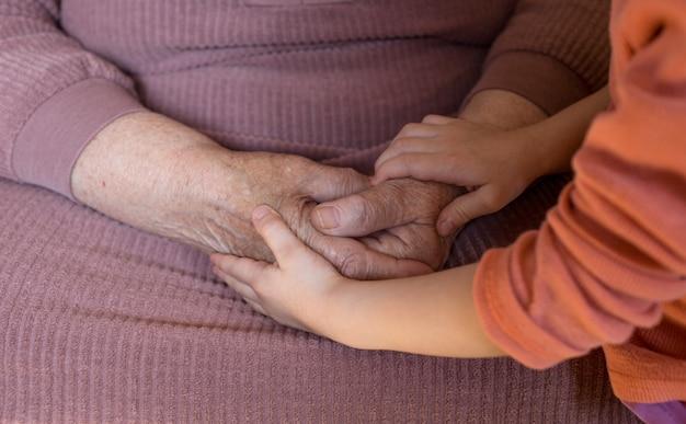 Close-up van de handen van een oudere oude vrouw en een klein meisje. ouderdom en jeugd