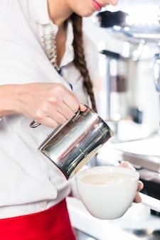 Close-up van de handen van een serveerster die melk in een koffiekop giet