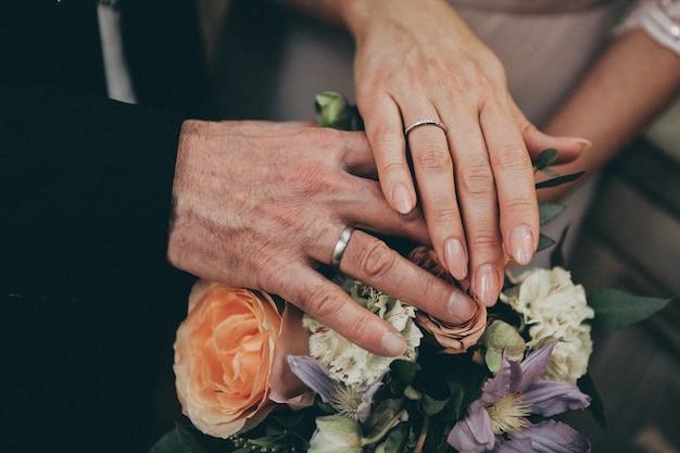 Close-up van de handen van een stel dat elkaar vasthoudt boven een boeket