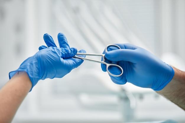 Close-up van de handen van een tandarts en verpleegster chirurg boven een operatiekamer tijdens een tandheelkundige implantaatoperatie.