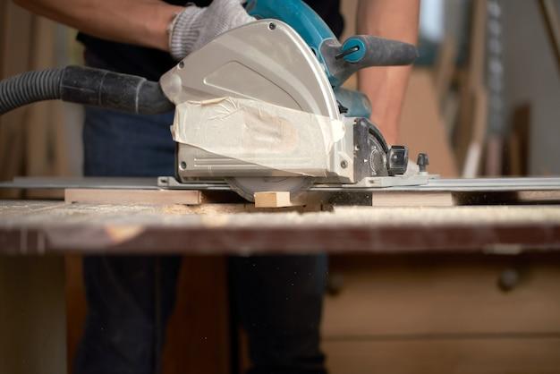 Close-up van de handen van een timmerman die houten planken zaagt met decoupeerzaag