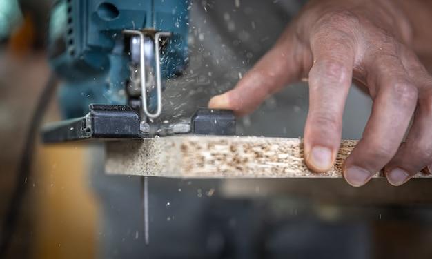 Close-up van de handen van een timmerman tijdens het zagen van hout met een decoupeerzaag.