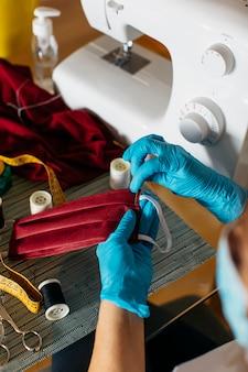 Close-up van de handen van een vrouw die een masker van het doekgezicht naaien