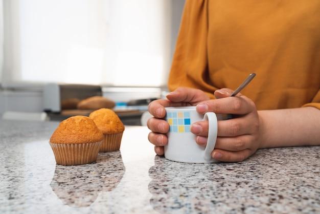 Close-up van de handen van een vrouw die haar handen opwarmen met een kop hete thee en wat muffins op een tafel