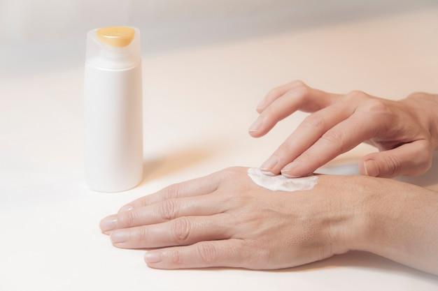 Close up van de handen van een vrouw die voor zichzelf zorgt door met twee vingers op de achterkant van haar linkerhand crème te wrijven