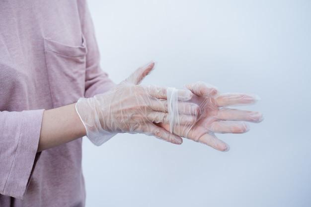 Close-up van de handen van een vrouw die wegwerphandschoenen verwijderen tijdens de coronavirus pandemie