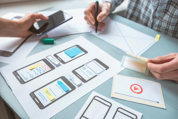 Close-up van de handen van een webdesigner ontwikkelen van toepassingen voor mobiele telefoons.