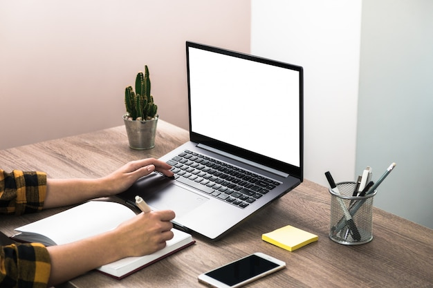 Close-up van de handen van een zakenvrouw, student of freelancer in geel shirt maken van aantekeningen in haar notitieblok. de studie is macht