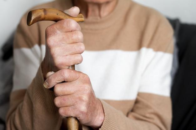 Close-up van de handen van een zeer bejaarde persoon in een beige concept van de sweatergezondheid