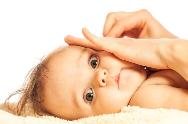 Close-up van de handen van een zorgzame jonge moeder borstelt de oren van een mooi klein meisje van zes maanden