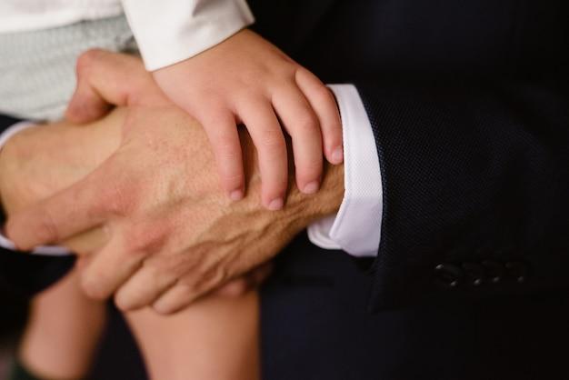 Close-up van de handen van het kind die op de vuisten van zijn vader rusten.