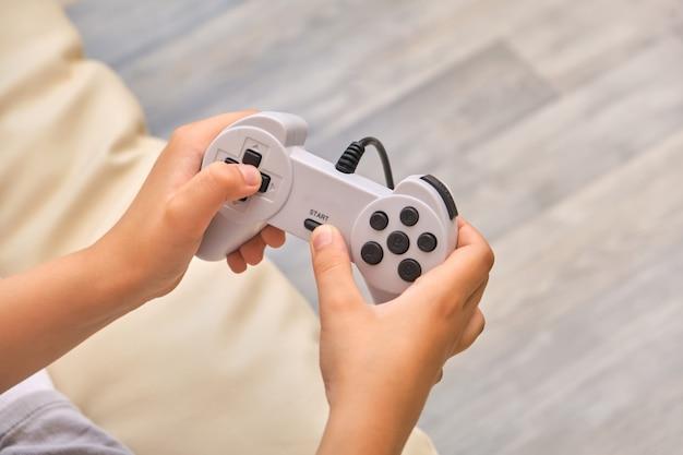 Close-up van de handen van het kind met een joystick-controller terwijl je thuis een videogame speelt, thuis op de bank zit at
