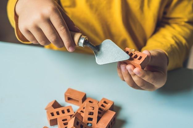 Close up van de handen van het kind spelen met echte kleine bakstenen aan de tafel
