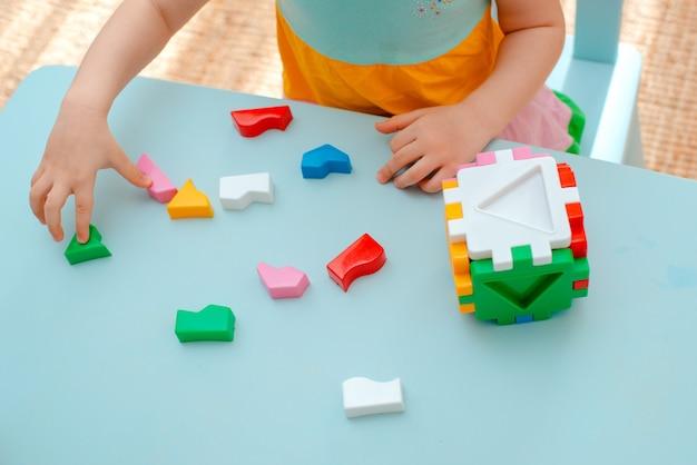 Close-up van de handen van het kind verzamelen puzzelsorteerder. kubus met ingevoegde geometrische vormen en gekleurde plastic blokken.