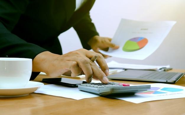 Close-up van de handen van zakenlieden die calculators drukken