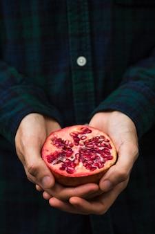 Close-up van de handholding van een persoon gehalveerde granaatappel