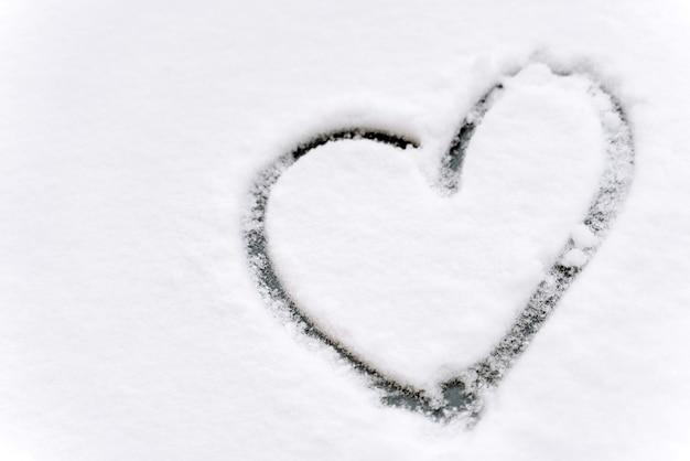 Close-up van de hartvorm getekend op de voorruit van een auto bedekt met verse witte sneeuw. winterconcept. stock foto