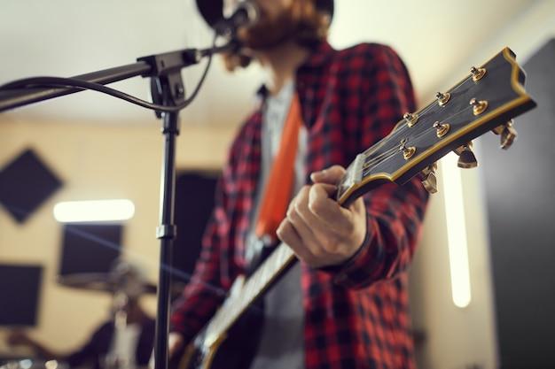 Close-up van de hedendaagse man met gitaar tijdens het zingen naar de microfoon tijdens de repetitie