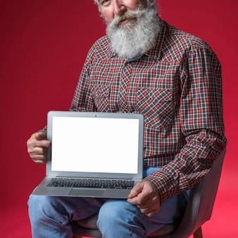 Close-up van de hogere mens die digitale tablet met lege witte het schermvertoning tonen tegen rode achtergrond