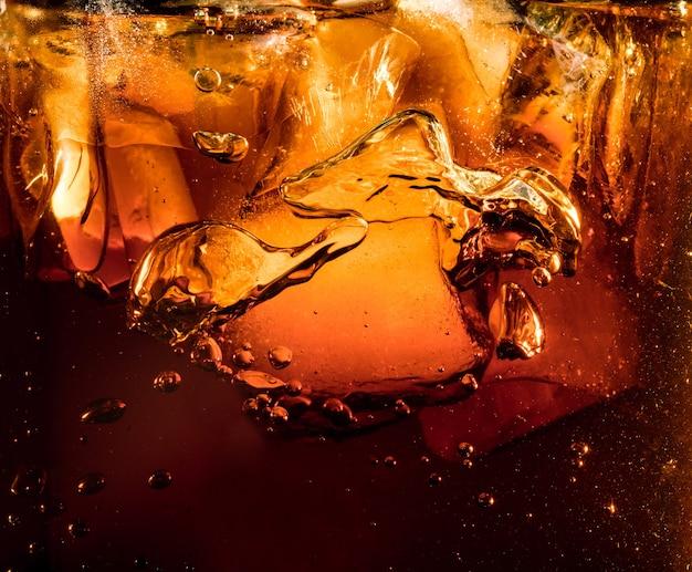 Close-up van de ijsblokjes op donkere cola achtergrond. textuur van het koelen van de zoete zomerdrank met schuim en macrobellen op de glasmuur. bruisen of drijven naar de bovenkant van het oppervlak.