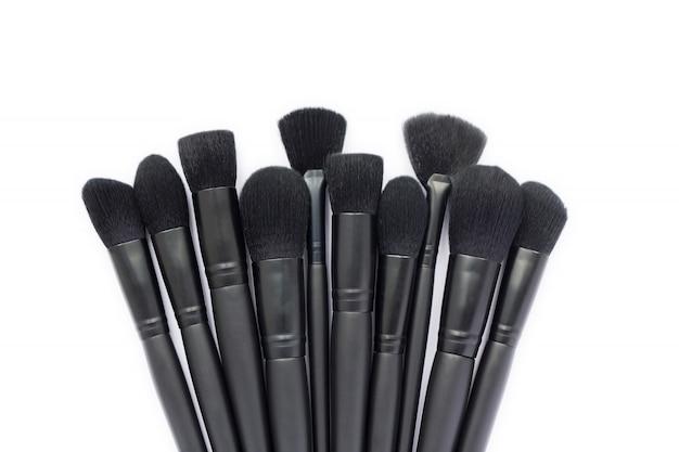 Close-up van de inzameling van make-upborstels die op witte ruimte wordt geïsoleerd