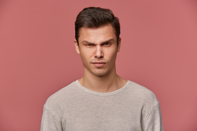 Close up van de jonge knappe strikte man draagt in fundamentele lange mouw, kijkt naar de camera met een boze uitdrukking, geïsoleerd op roze achtergrond.