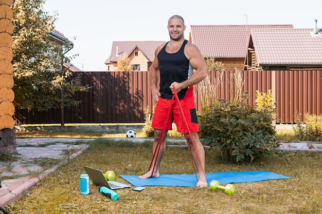 Close-up van de jonge man gaat in de zomerdag thuis sporten in de achtertuin. jonge sportman die oefening met sportrubber doet