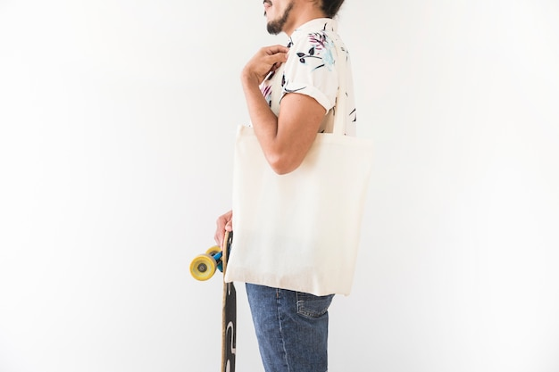Close-up van de jonge man met een schoudertas bedrijf skatingboard