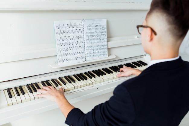 Close-up van de jonge man op zoek naar muzikale blad piano spelen