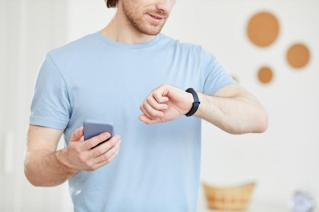Close-up van de jonge mens die zijn horloge bekijkt en zijn tijd controleert met mobiele telefoon