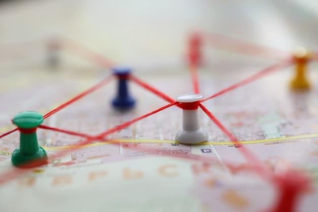 Close-up van de kaart gemarkeerd met bewegingspaden met rode draden. plattegrond van straat met knopen die route vormen. voetgangersroute door de stad. navigatie concept
