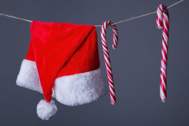 Close-up van de kerstman-hoed, en het suikergoed die van het nieuwjaar op een waslijn hangen.
