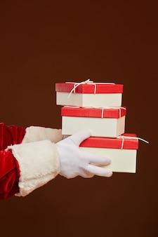 Close-up van de kerstman in handschoenen met stapel kerstcadeautjes