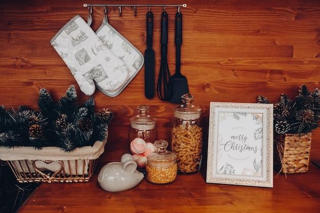 Close-up van de keukentafel over houten achtergrond met vaas met dennenboom en dennenappels, containers met granen, uien en keukengerei.