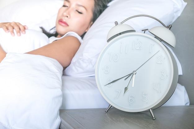 Close-up van de klok met een vrouw slapen in de achtergrond