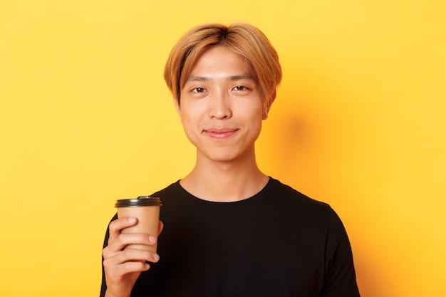 Close-up van de knappe blonde aziatische mens die koffie drinkt en tevreden glimlacht, die zich over gele muur bevindt