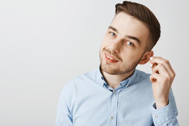 Close-up van de knappe oortelefoon van de jongemanstijging om te horen wat u zegt