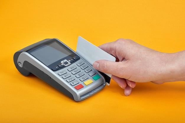 Close-up van de knoppen van de betalingsmachine met menselijke hand die plastic kaart dichtbij op geel houdt