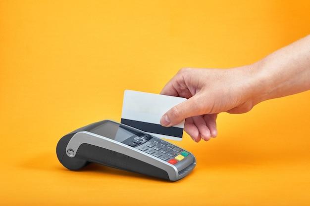 Close-up van de knoppen van de betalingsmachine met menselijke hand met plastic kaart