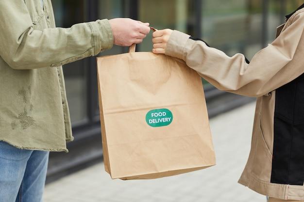Close-up van de koerier die het pakket doorgeeft aan de klant die de levering van eten bestelt