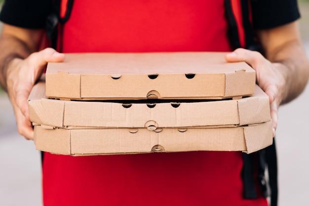 Close-up van de koeriershanden en het pizzaportret van de bezorger die de kartonnen pizzadoos vasthoudt