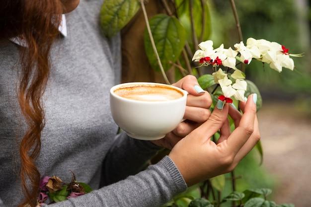 Close-up van de koffiekop van de vrouwenholding