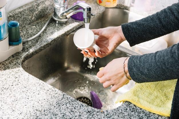 Close-up van de kop van de de handwas van een vrouw in keukengootsteen