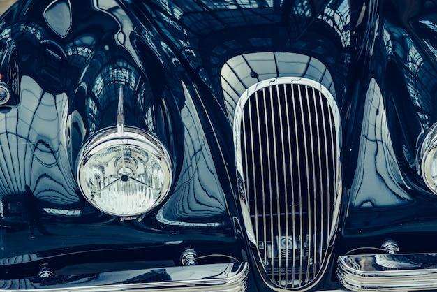 Close-up van de koplampen en de voorbumper op uitstekende auto