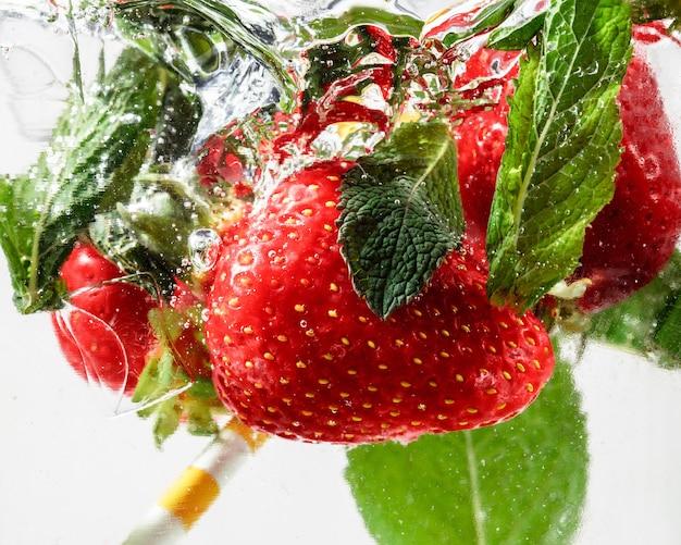 Close-up van de koude en verse limonade met aardbeienmuntblaadjes en ijsblokjes