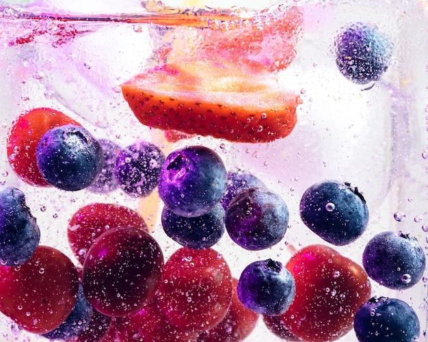 Close-up van de koude en verse limonade met heldere bessen en ijsblokjes in neonlicht. textuur van verkoelende zomerdrank met macrobellen op glas. bruisend of zwevend naar de bovenkant van het oppervlak.
