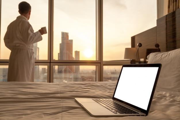 Close-up van de laptop op het bed met een man in badjas achtergrond